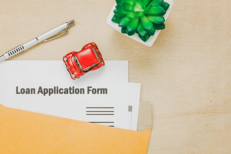 Application form, car, pen, and tree on wooden table
