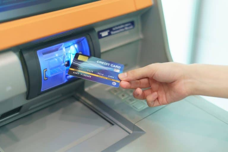 Woman hand inserting a credit card, into bank machine to withdraw cash